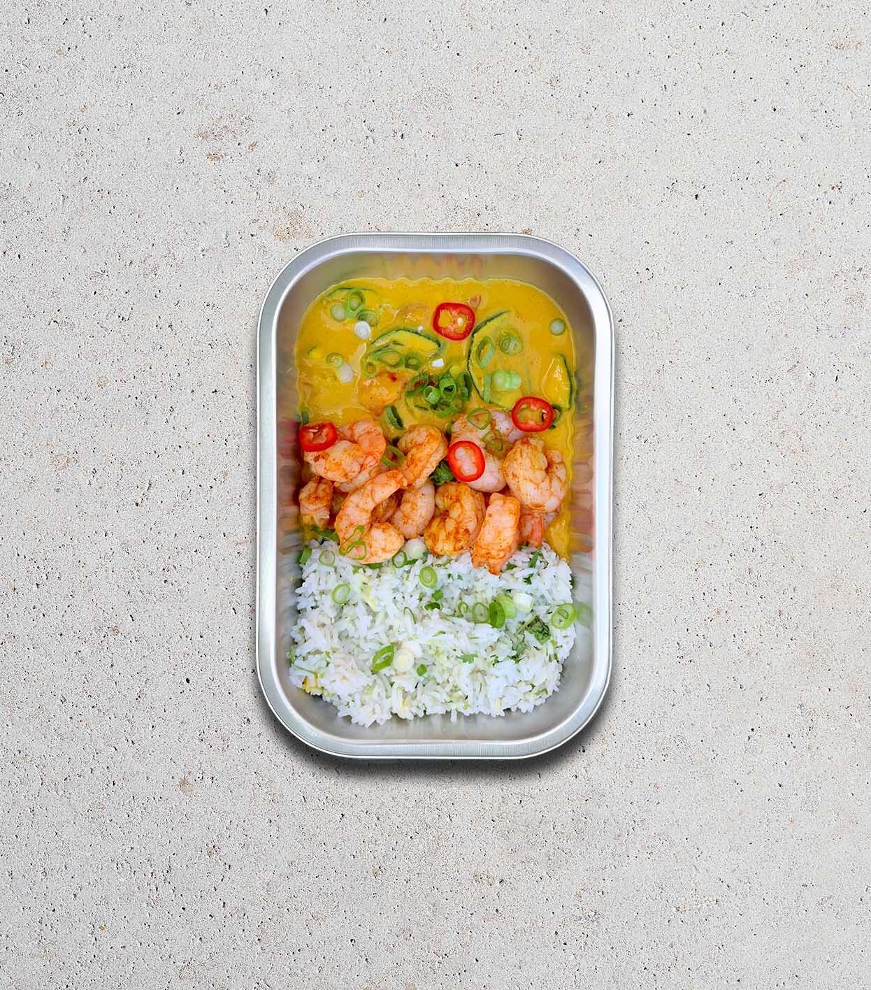 gezonde warm gerecht met gele scampi curry groenten rijst en cashewnoten in meeneemverpakking
