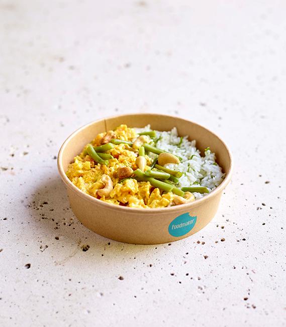 gezonde warm gerecht met gele curry groenten rijst en cashewnoten in meeneemverpakking
